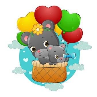 Le bébé ours tient les jumelles dans le panier volant avec sa mère de l'illustration