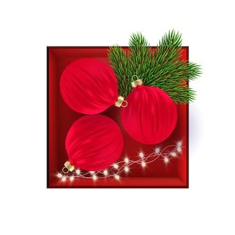 Belle boîte cadeau rouge avec des boules de noël rouges réalistes, des branches d'arbres de noël et une guirlande