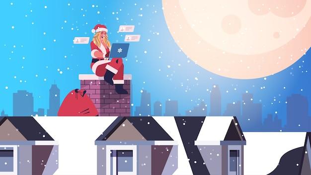 Belle femme en costume de père noël assis sur la cheminée fille utilisant un ordinateur portable bonne année joyeux noël vacances célébration concept cityscape backgound illustration vectorielle horizontale pleine longueur