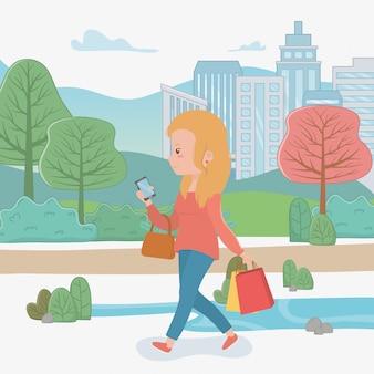 Belle femme marchant dans le parc à l'aide de smartphone