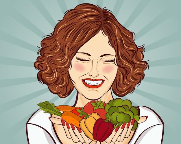 Belle femme rousse avec des légumes dans ses mains