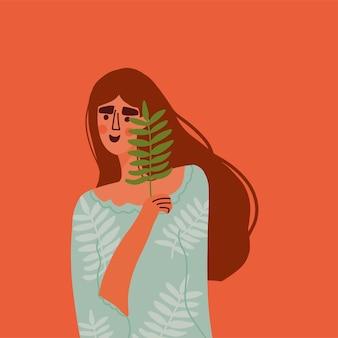 Une belle fille aux cheveux longs tient une feuille tropicale sur son visage beauty concept