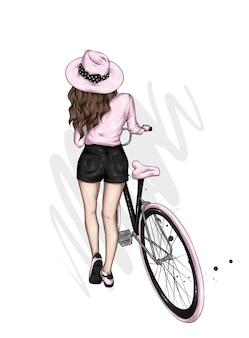 Belle fille dans des vêtements élégants et un vélo