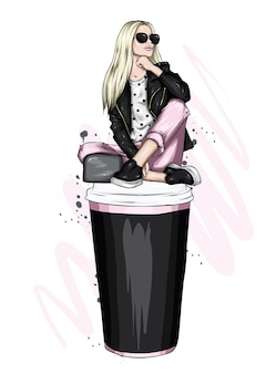 Belle fille dans des vêtements élégants et un verre de café