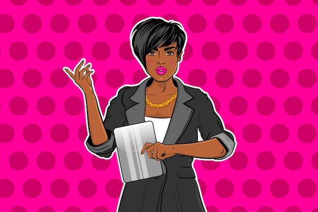 Belle fille noire de pop art en costume travaillant sur tablette