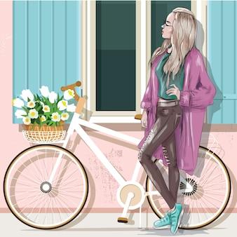 Belle fille en vêtements décontractés avec vélo et façade du bâtiment