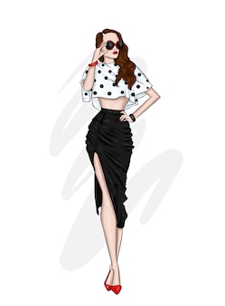 Une belle grande fille aux longues jambes dans une jupe élégante, un chemisier et des chaussures à talons hauts.