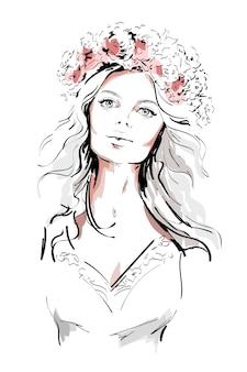 Belle jeune femme avec une couronne de fleurs dans les cheveux longs.