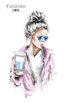 Belle jeune femme tenant une tasse de café en plastique