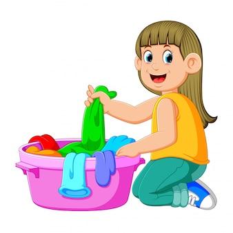 Belle jeune femme tient un bassin avec lessive