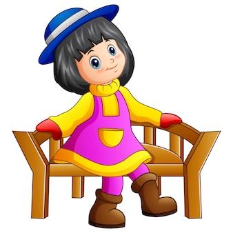 Belle petite fille assise sur un banc en bois