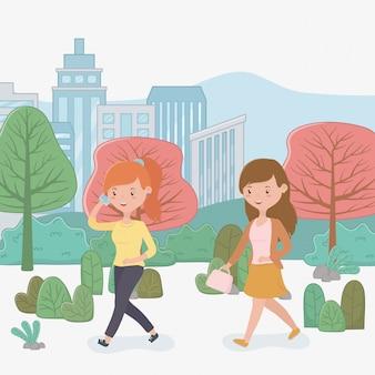 Belles femmes marchant dans le parc à l'aide de smartphones
