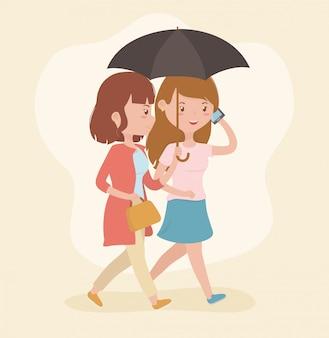 Belles femmes marchant en utilisant des smartphones
