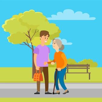 Une bénévole aide une vieille mamie à porter un sac dans un parc
