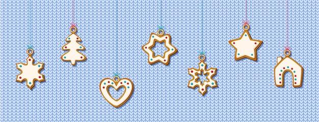 Biscuits de pain d'épice de noël suspendus sur fond bleu tricoté. biscuits festifs en forme de maison et arbre de noël, étoile et flocon de neige et coeur pour carte de voeux de vacances. illustration vectorielle
