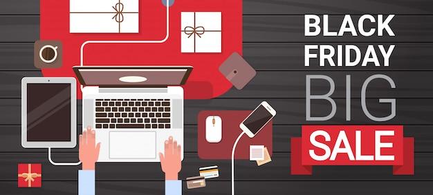 Black friday big sale signe sur la main en tapant sur un ordinateur portable, vue de dessus