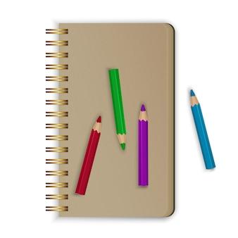 Bloc-notes en spirale réaliste. carnet de croquis réaliste avec des crayons de couleur.