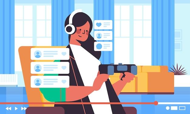 Blogger femelle enregistrement processus de jeu blog en ligne streaming en direct blogging vlog popularité concept fille jouer à des jeux vidéo salon intérieur portrait horizontal