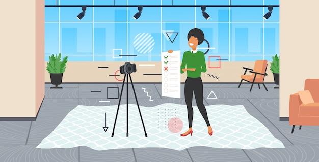 Blogger présentant la liste de contrôle enquête formulaire d'examen femme enregistrement vidéo en ligne avec caméra sur trépied résultat évaluation blogging concept moderne bureau intérieur pleine longueur horizontale