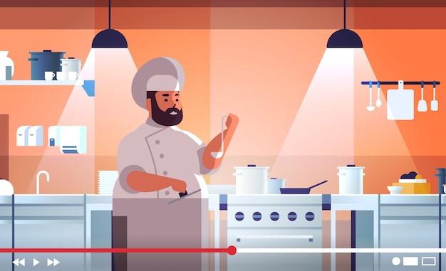 Blogueur alimentaire enregistrement vidéo en ligne chef en surpoids en uniforme cuisson dans la cuisine blogging concept homme vlogger expliquant comment cuisiner un plat portrait horizontal