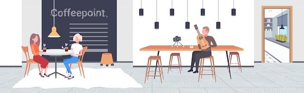 Blogueur de musique jouant de la guitare en direct concept de blog musical afro-américain enregistrement vidéo à l'aide de la caméra sur un trépied intérieur de café moderne horizontal pleine longueur