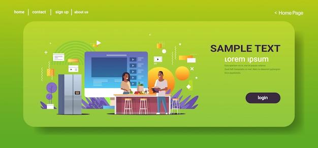 Les blogueurs alimentaires enregistrement vidéo en ligne afro-américain homme femme cuisine ensemble dans la cuisine blogging concept couple vloggers expliquant comment faire cuire un plat espace copie horizontale pleine longueur