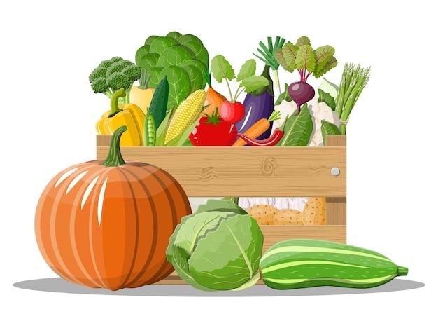 Boîte en bois pleine de légumes isolé sur blanc