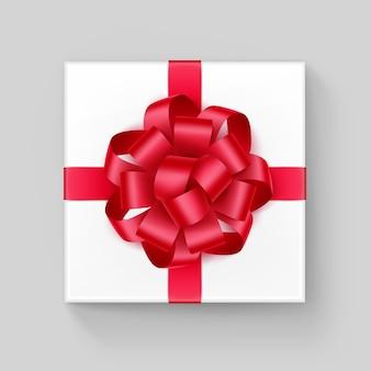 Boîte-cadeau carré blanc avec noeud de ruban rouge brillant close up vue de dessus isolé sur fond