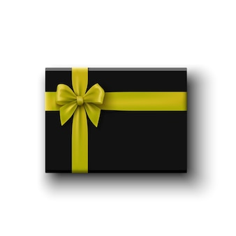 Boîte cadeau noire avec noeud jaune sur blanc, vue du dessus