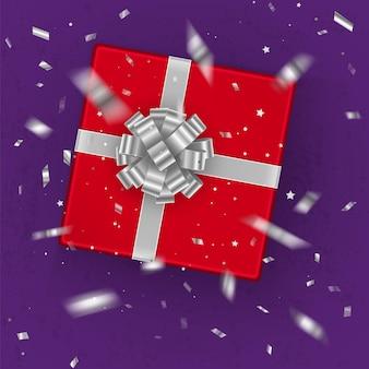 Une boîte cadeau rouge réaliste décorée d'un arc en argent, vue de dessus.