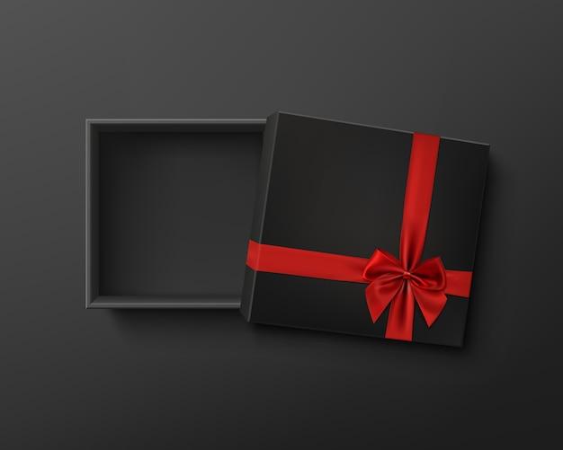 Boîte cadeau vide noire ouverte avec ruban rouge et arc sur fond sombre.