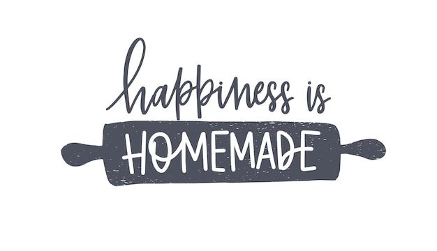 Le bonheur est une phrase maison écrite à la main avec une police calligraphique cursive ou un script sur un rouleau à pâtisserie
