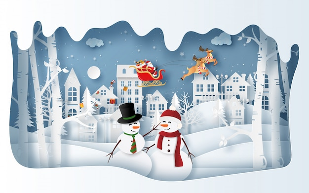 Bonhomme de neige au village en hiver avec le père noël