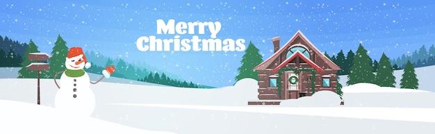 Bonhomme de neige près de l'hiver maison en bois couverte de neige dans la forêt de pins joyeux noël bonne année vacances célébration concept paysage