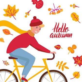Bonjour automne. jeune homme au chapeau tricoté sur un vélo.
