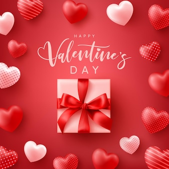Bonne affiche de la saint-valentin ou une bannière avec des coeurs doux et une jolie boîte-cadeau sur le rouge