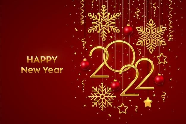 Bonne année 2022. numéros métalliques dorés suspendus 2022 avec des flocons de neige brillants, des étoiles métalliques 3d, des boules et des confettis sur fond rouge. modèle de carte de voeux ou de bannière de nouvel an. vecteur.