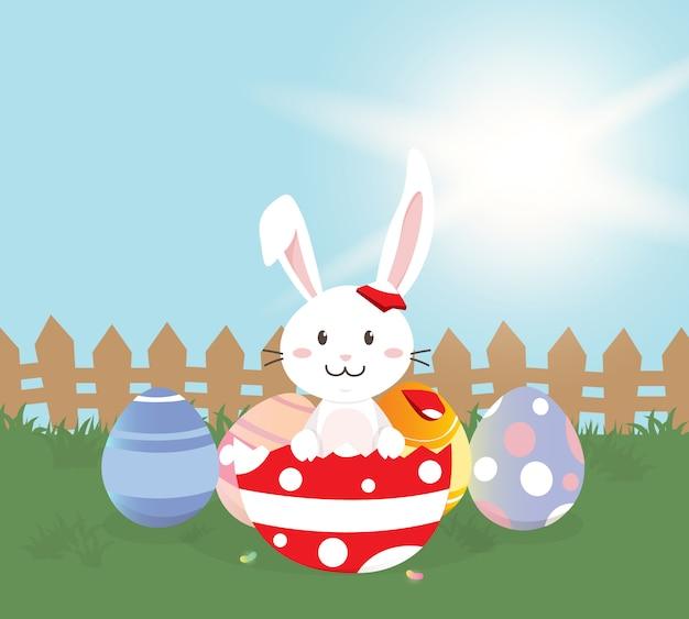 Bonne carte de voeux de pâques, joli lapin avec des oeufs de pâques colorés dans le champ de printemps. illustration vectorielle