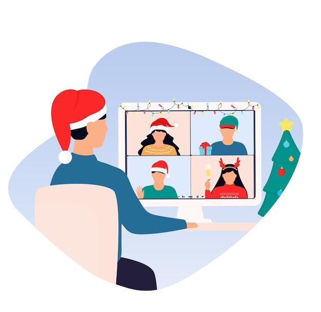 Bonne fête en ligne du nouvel an. un homme portant un bonnet de noel salue ses amis lors d'un appel vidéo virtuel.