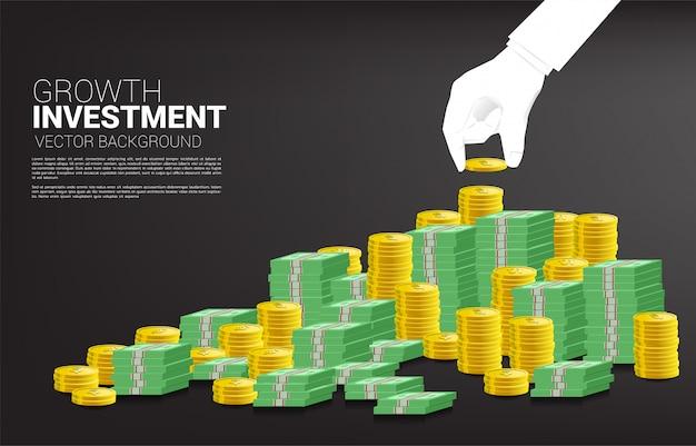 Bouchent la main de l'homme d'affaires avec pièce de monnaie et pile de pièces d'or et de billets de banque. concept d'investissement de succès et de croissance dans les affaires