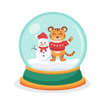 Boule à neige de noël avec un tigre et un bonhomme de neige à l'intérieur