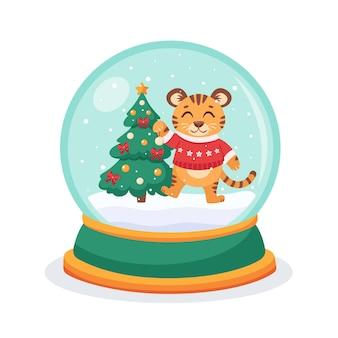 Boule à neige de noël avec un tigre et un sapin à l'intérieur de la sphère boule à neige