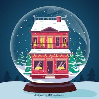 Boule de noël fond avec une belle maison rouge chutes de neige