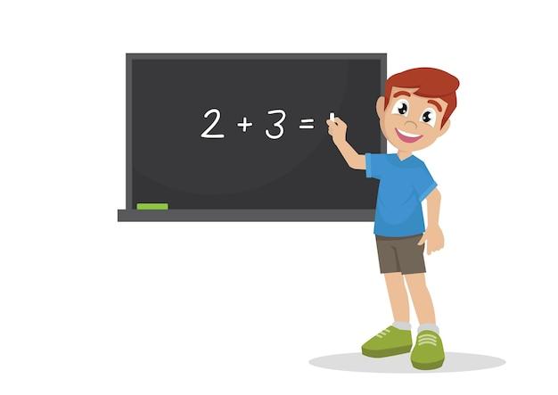 Boy est debout près de la commission scolaire avec de la craie à la main.