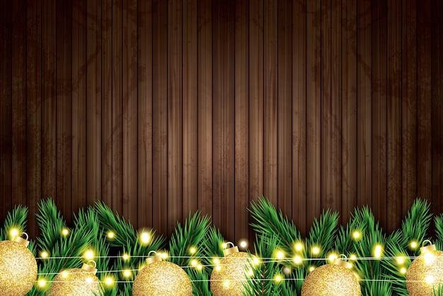 Branche de sapin avec boules de noël dorées et chaîne de néon sur fond de bois.