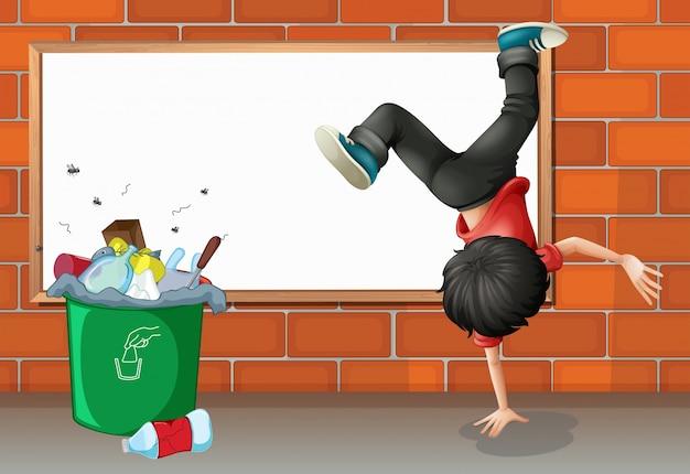 Un breakdance garçon près d'une poubelle avec un tableau vide