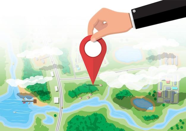 Broche de localisation en main avec vue aérienne du village