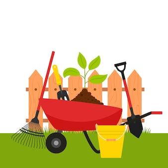 Une brouette de jardin avec une plante et des outils sur le fond d'une clôture et de l'herbe.