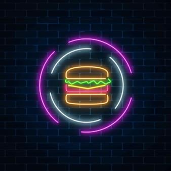 Burger rougeoyant au néon signe dans des cadres de cercle sur un fond de mur de brique sombre. symbole de panneau d'affichage lumineux fastfood.