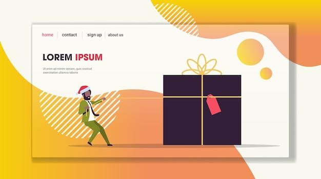 Businessman in santa hat pulling big gift box joyeux noël nouvel an vacances d'hiver célébration concept page de destination